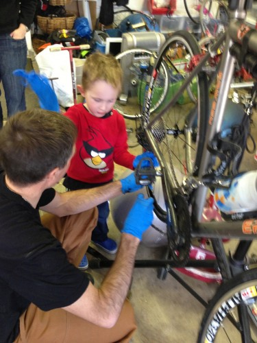 Pascal was helping his dad put a new chain on his bike.  He made sure he had gloves on too.