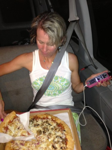Catherine in the back seat multi-tasking, divvying up the pizza that we pre-ordered and ate in the car and checking on the thunderstorms ahead on her phone.