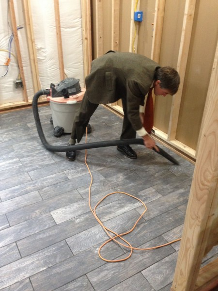 Vincent cleaning grouts lines in a suit.