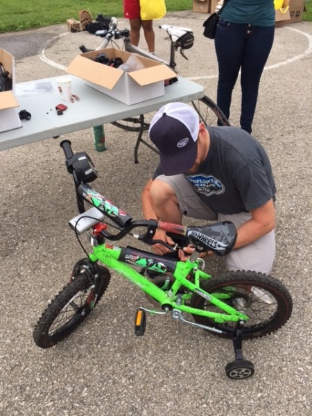 Dan Hughes, owner of Sunflower Bike shop, mounting some lights on one of the kid's bikes.