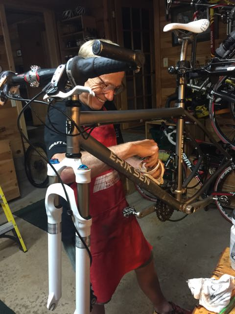 Dennis wearing an apron, using a toothbrush to clean his bike.